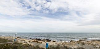 Het paar picnicking op een strand Stock Afbeeldingen