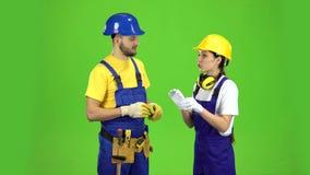 Het paar professionele bouwers spreekt onder zich Het groene scherm stock videobeelden
