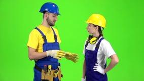 Het paar professionele bouwers spreekt onder zich Het groene scherm Langzame Motie stock video