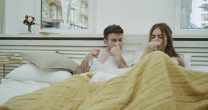 Het paar in pyjama's die op bed bepalen heeft een griep, hoestend en voelend niet goed bij allen, die warm iets drinken stock video