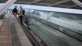 Het paar reizigers met bagage bevindt zich op roltrap die zich neer bewegen stock videobeelden