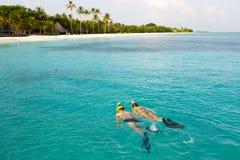 Het paar snorkelt in kristalwater in de Maldiven Stock Foto's