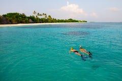 Het paar snorkelt in kristalwater in de Maldiven Royalty-vrije Stock Afbeeldingen
