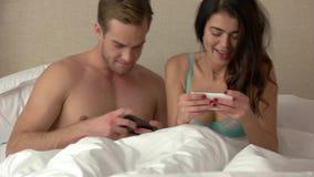 Het paar speelt op telefoons stock video