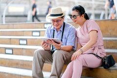 Het paar van Aziatische oude man en vrouwentoerist bekijkt tablet tijdens het reizen van grote stad Deze foto bevat ook concept royalty-vrije stock fotografie