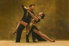 Het paar van de dansbalzaal in gouden kleding die op studioachtergrond dansen stock foto's