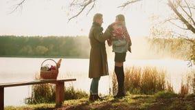 Het paar van de herfst meisje op de rug van de jongen Mooi paar in warme kleren die zich dichtbij het meer bevinden, waar weerspi stock videobeelden