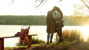 Het paar van de herfst meisje op de rug van de jongen Mooi paar in warme kleren die zich dichtbij het meer bevinden, waar weerspi stock footage