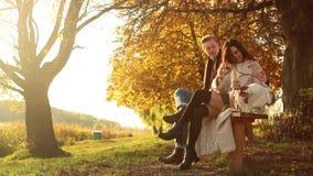Het paar van de herfst meisje op de rug van de jongen Mooi paar in warme kleren die zich dichtbij het meer bevinden, waar weerspi stock video
