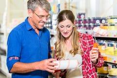 Het paar van de huisverbeteraar het kopen verf en schildershulpmiddelen in ijzerhandel stock afbeeldingen