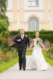 Het paar van de jonggehuwde - bruid en bruidegom - in een park runn Royalty-vrije Stock Fotografie