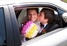 Het paar van de jonggehuwde het kussen in huwelijksauto Stock Fotografie