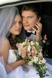 Het paar van de jonggehuwde in limo van de huwelijksauto Royalty-vrije Stock Afbeeldingen