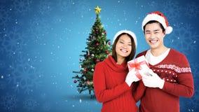 Het paar van de Kerstmiswinter met Kerstboom en gift stock footage