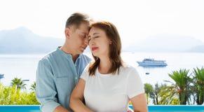 Het paar van de middenleeftijdsfamilie bij de vakantietoevlucht op overzeese achtergrond De de zomermensen reizen naar tropisch s royalty-vrije stock foto's