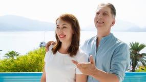 Het paar van de middenleeftijdsfamilie bij de vakantietoevlucht op overzeese achtergrond De de zomermensen reizen naar tropisch s royalty-vrije stock fotografie