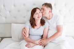 Het paar van de middenleeftijdsfamilie in witte slaapkamer in bed De vrouw van de echtgenootkus Liefde en Romaans Gezonde Verhoud stock afbeeldingen