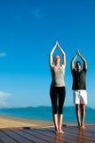 Het Paar van de yoga door Oceaan Stock Foto