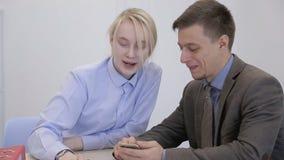 Het paar van financiële analytics geniet van de verhoging bitcoin prises kijkend aan het scherm van cellphone stock video