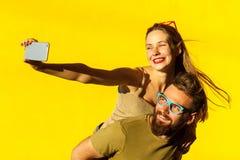 Het paar van het geluk piggyback Selfie stock foto's