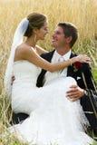 Het paar van het huwelijk in lang gras buiten Stock Foto