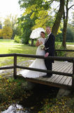 Het paar van het huwelijk op houten brug in de herfst Royalty-vrije Stock Foto