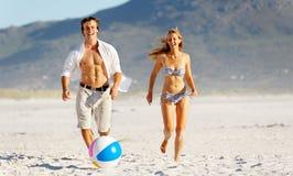 Het paar van het strand het spelen met bal Stock Foto