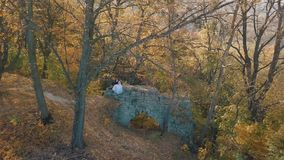 Het Paar van het huwelijk Mooie bruidegom en bruid die op overblijfselen van een vernietigd gebouw in de bos Gelukkige familie zi stock video