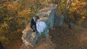 Het Paar van het huwelijk Mooie bruidegom en bruid die op overblijfselen van een vernietigd gebouw in de bos Gelukkige familie zi stock videobeelden