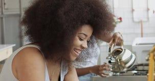 Het paar van jonge gemengde rasvrouw met afro groot haar heeft een ontbijt op keuken stock video