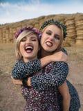 Het paar van jonge sexy lesbische meisjes laught in licht kleedt flirt, spel laught en huisdier binnen in het weiland in hayloft Royalty-vrije Stock Fotografie