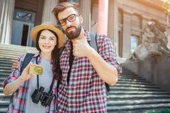 Het paar van jonge toeristentribune outisde bij treden en stelt op camera Zij houdt gouden kaart in hand De grote duim van de men royalty-vrije stock afbeeldingen