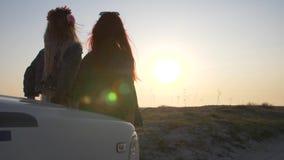 Het paar van jonge vrouwen zit op de bumper en geniet van de zonsondergang stock video
