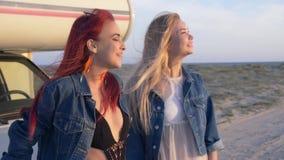 Het paar van jonge vrouwen zit op de bumper en geniet van de zonsondergang bij zandig strand met weg stock footage