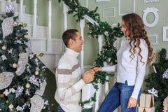 Het paar van minnaars bevindt zich op de witte treden in het huis en glimlacht op de vooravond van de Kerstmisvakantie De kerel n royalty-vrije stock afbeelding