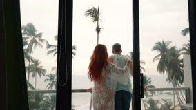 Het paar van minnaars bewondert de oceaanmening over het terras stock videobeelden