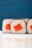 Het paar van smakelijke Japanner rolt met zalm, rijst en nori op hemel Stock Foto's