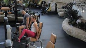 Het paar van sportspeople beëindigt been het uitspreiden exersice op de speciale machine in de luxegymnastiek stock video