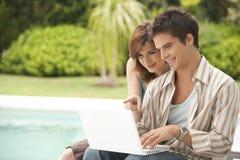Het Paar van Technologie van het huis met Laptop door Pool Stock Afbeelding