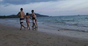 Het Paar van het twee Mengelingsras het Lopen Strand bij Zonsondergang het Spreken, de Mededeling van de Toeristengroep, Jonge Ge stock video