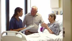 Het Paar van verpleegsterstalking to senior in het Ziekenhuiszaal stock video