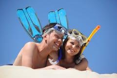 Het paar in vinnen en onderwatermaskers ligt royalty-vrije stock foto