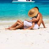 Het paar in wit ontspant op een strand in de Maldiven Stock Afbeelding
