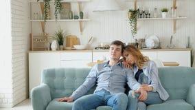 Het paar zit op comfortabele blauwe bank lettend op TV in moderne keuken stock video
