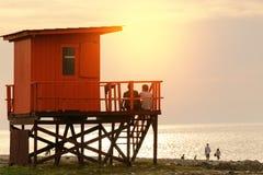 Het paar zit op de badmeestertoren op het strand, mensen a stock afbeeldingen