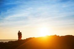 Het paar zit op de rots en wacht op zonsondergang stock foto's