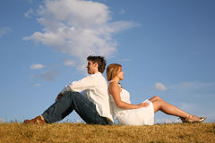 Het paar zit op weide Stock Foto