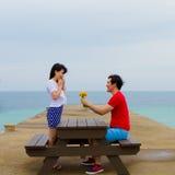 Het paar zit samen bij de lijst dichtbij het strand stock afbeelding