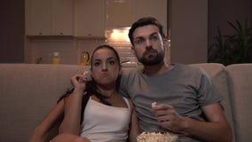 Het paar zit samen op bank en let op TV Zij nemen en eten popcorn van kom De kerel richt vooruit Het meisje gaat akkoord met stock video