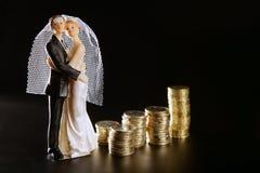 Het paarbeeldje van het huwelijk en gouden muntstukken Royalty-vrije Stock Afbeeldingen
